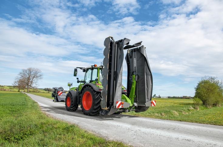 Fendt Traktor mit Fendt SafetySwing zur EInklappung des Fendt Slicer 860 fährt auf einer Straße