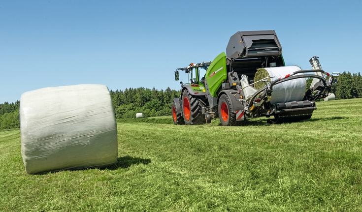 Fendt Traktor zieht Fendt Rotana 130F Rundballenpresse über Wiese mit foliengebundenen Heuballen