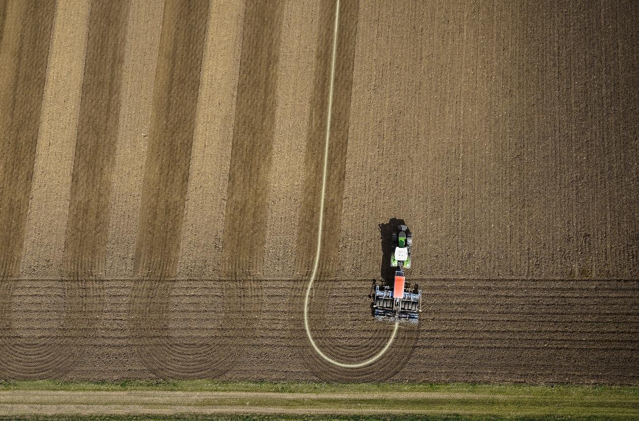 Obersicht Fendt 900 Vario bearbeitet Feld mit Anbaugerät in sehr geraden Spuren
