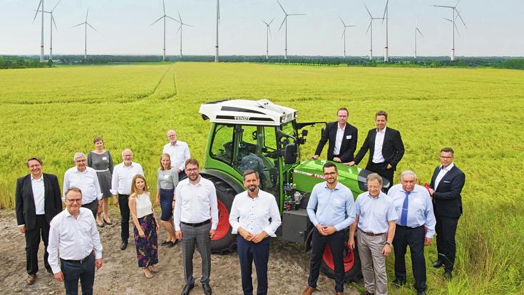 Fendt e100 Vario steht hinter einer Gruppe von Menschen mit Hintergrund von Windkraftwerken