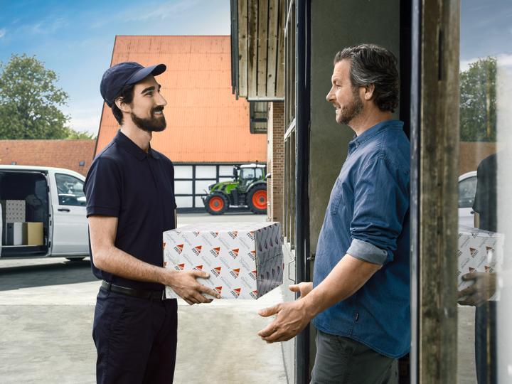 Fendt Kunde steht vor seiner Haustür und bekommt von einem AGCO Mitarbeiter ein Paket mit Ersatzteile überreicht.