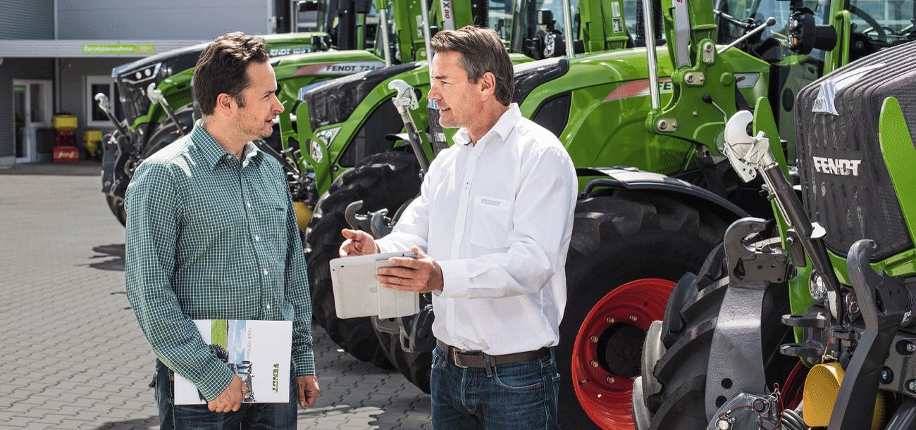 Kunde steht mit Händler vor drei Fendt Traktoren und lässt sich über Finanzierung beraten.