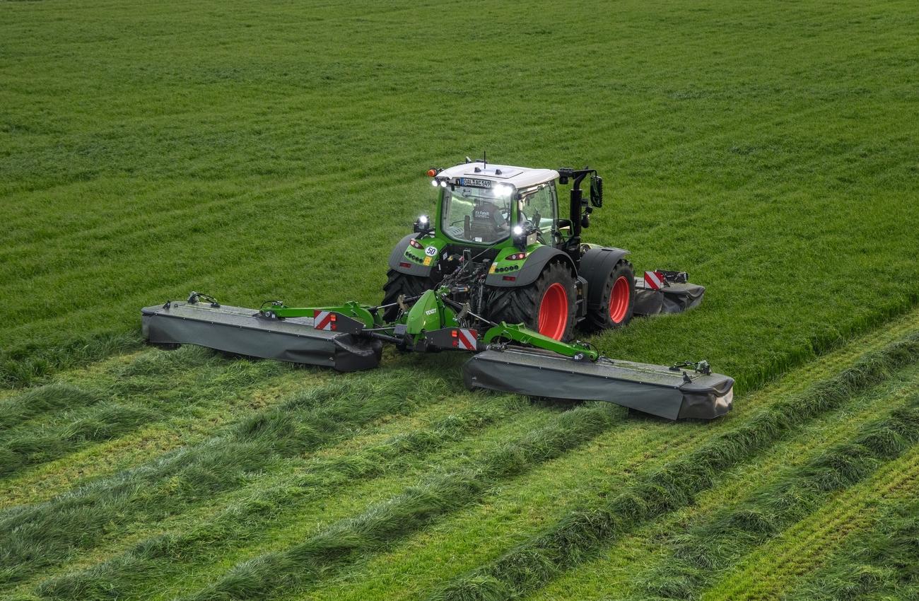 Fendt Traktor mäht bei eingeschaltetem Licht mit Fendt Slicer Front-Heckmähwerkkombination über Wiese