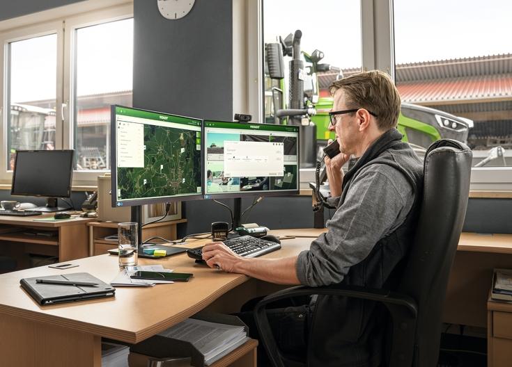 Mann sitzt am Schreibtisch vor FendtONE Webanwendung und im Hintergrund Fendt Traktoren