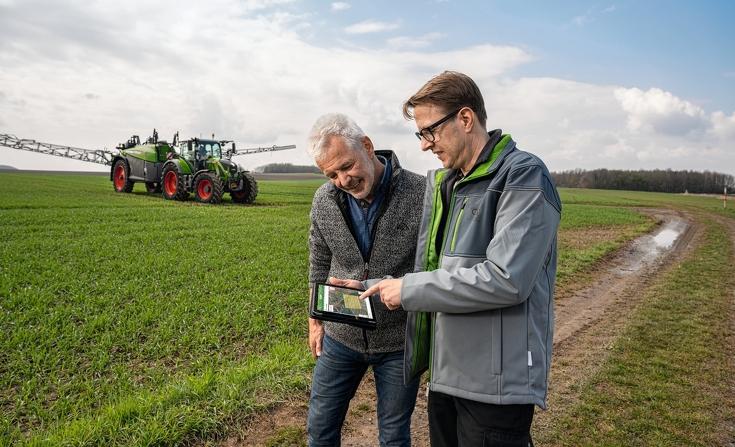 Zwei Landwirte prüfen bei FendtONE auf dem IPad die Daten des hinter Ihnen stehenden Fendt Rogator 300