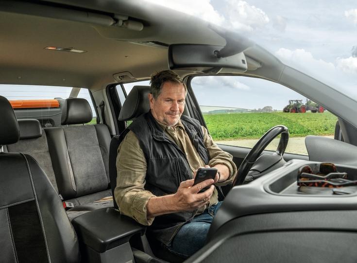Landwirt sitzt im Auto auf sein Handy schauend mit Fendt Traktor im Hintergrund