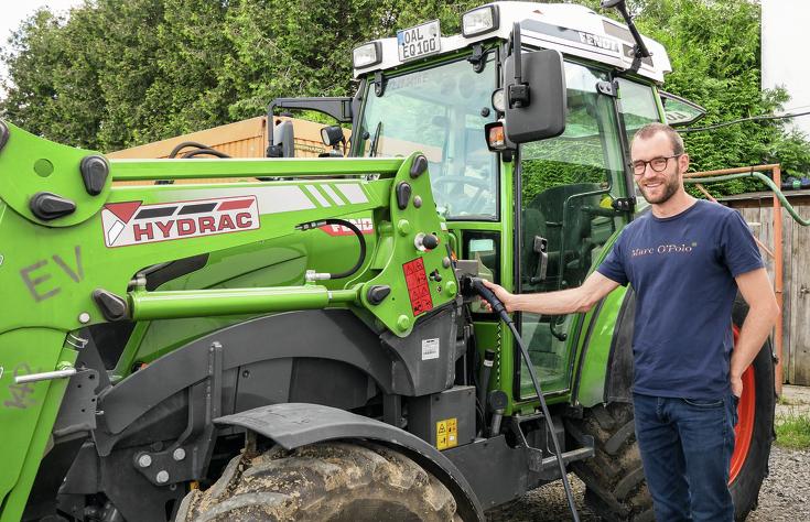Landwirt lädt den stehenden batteriebetriebenen Fendt e100 Vario mit Frontlader