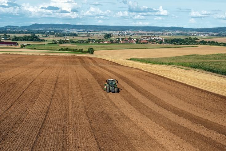 Fendt 500 Vario fährt mit Anbaugerät über weites Feld mit Dörfern im Hintergrund