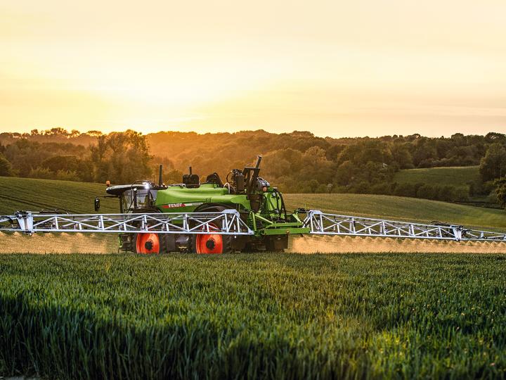 Selbstfahrende Pflanzenschutzspritze Fendt Rogator 600 auf einem Getreidefeld bei Sonnenuntergang.