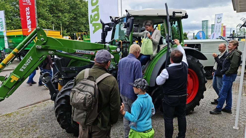 Besucher der Landwirtschaftsmesse betrachten den Fendt 211 Vario