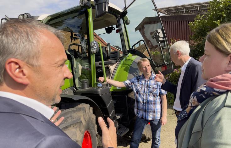 Vier Personen im Gespräch vor dem Fendt 314 Vario Traktor