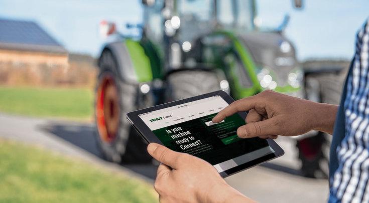 Hombre delante del tractor con una tablet en la mano que tiene abierta la aplicación Fendt Connect.