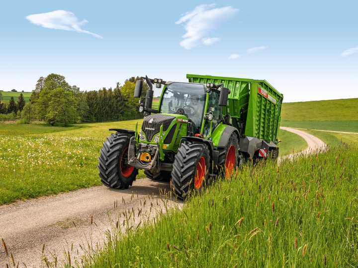 El nuevo Fendt 500 Vario circulando con un remolque auto-cargador por un camino en el campo.