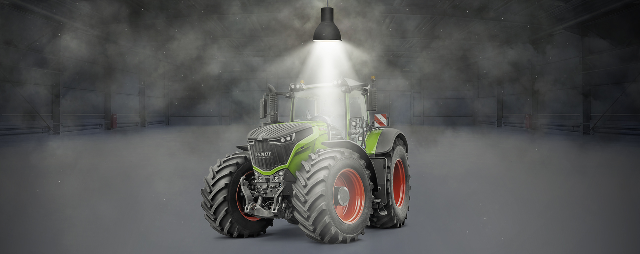Fendt 1000 Vario stands in a hall and is illuminated by a spotlight.