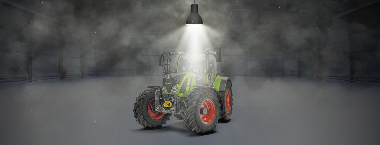 Fendt 500 Vario stands in a hall and is illuminated by a spotlight.