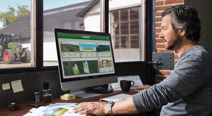 Mies istuu tietokoneensa ääressä ja käyttää Fendt Task Docia.