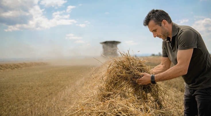 A man is checking the straw in front of the Fendt IDEAL.