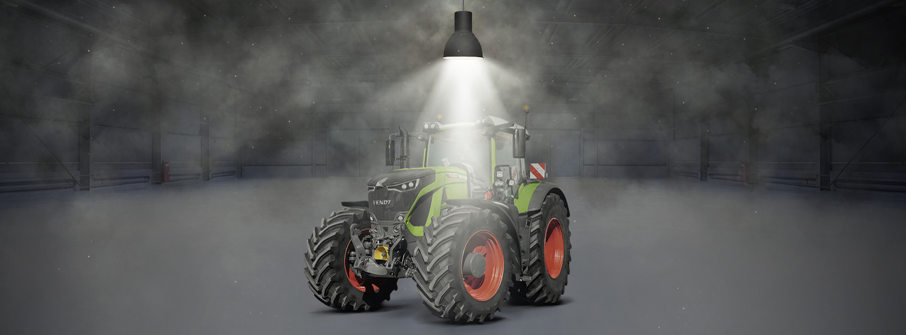 Fendt 900 Vario standing in a hall and illuminated by a spotlight.