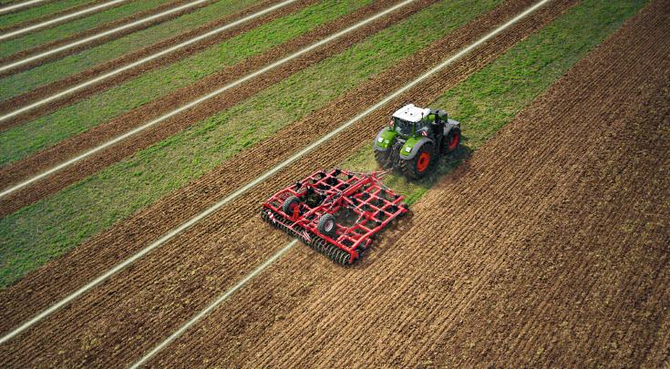 Il Fendt 1000 Vario lavora il terreno con un coltivatore.