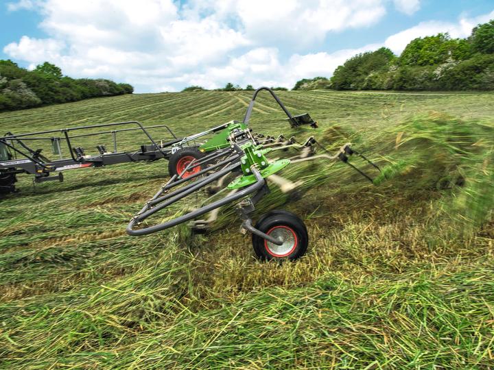 Spandi-voltafieno Fendt Twister su un campo durante la svolta. L'erba vola in aria.