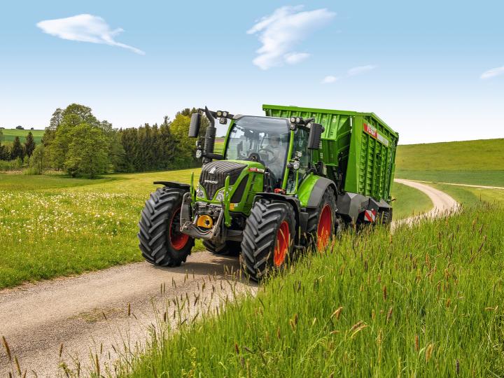 De nieuwe Fendt 500 Vario rijdt met opraapwagen over een veldweg.