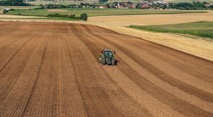 Fendt 500 Vario z zestawem uprawowo siewnym na polu z dalekiej perspektywy.