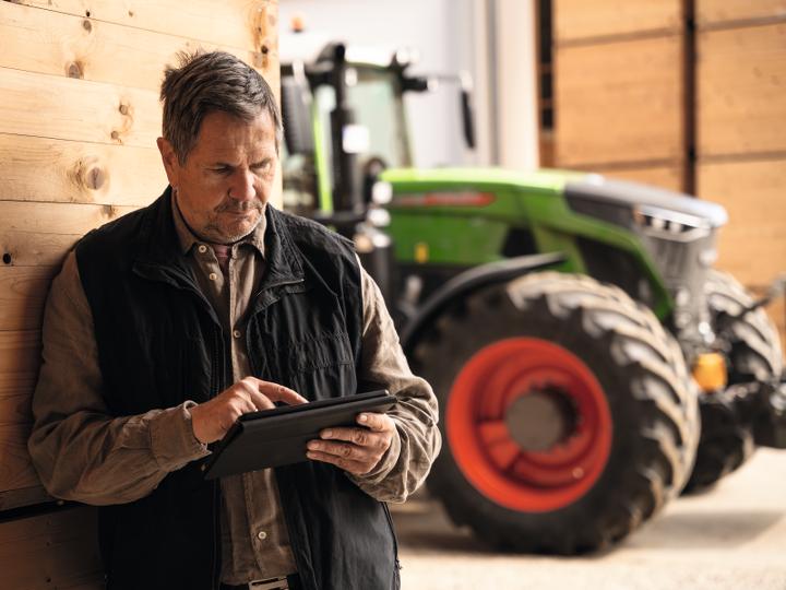 En lantbrukare står i en lada bredvid sin traktor och kontrollerar sina data på en surfplatta.