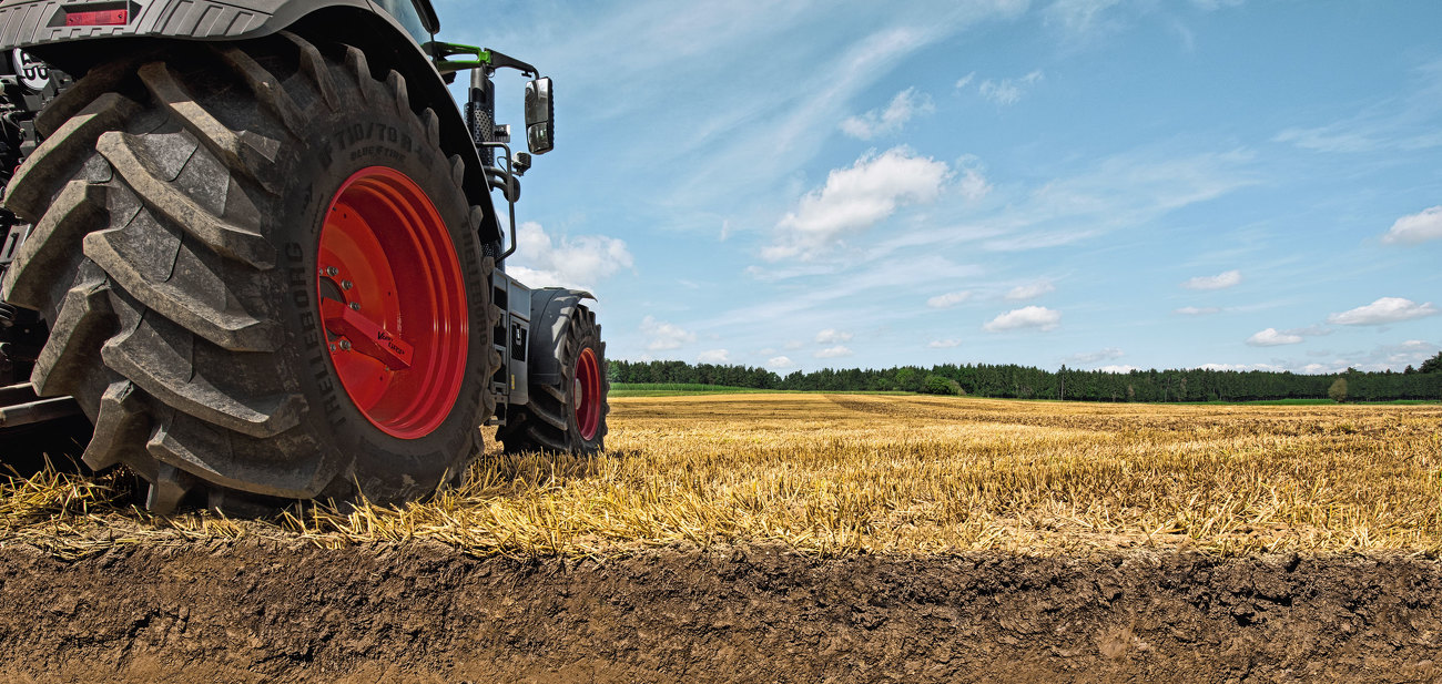 Fendt 900 Vario with integrated tyre pressure regulation system Fendt VarioGrip, shown stationary in a field. In the foreground you can see a cross-section of the soil.