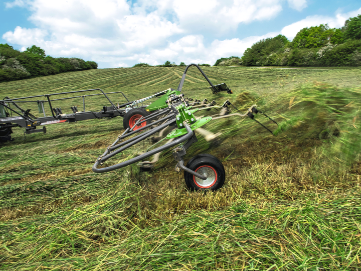 Fendt Twister tedder on a field during turning. Grass flies into the air.